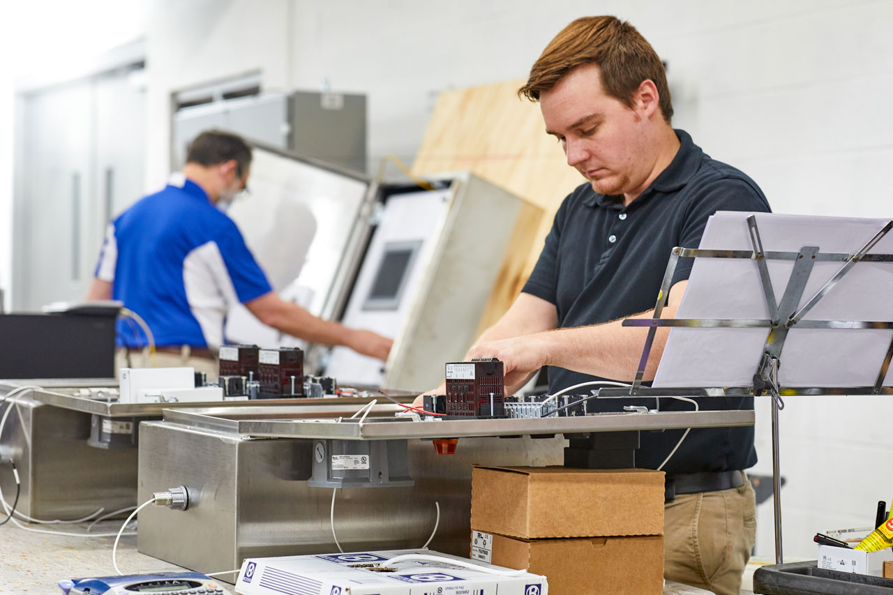 man with red hair assembling a control board for an industrial automation system