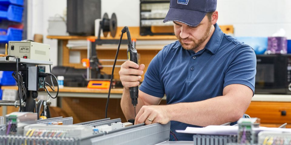 Man wearing a baseball cap adjusting components of a mechanical control board