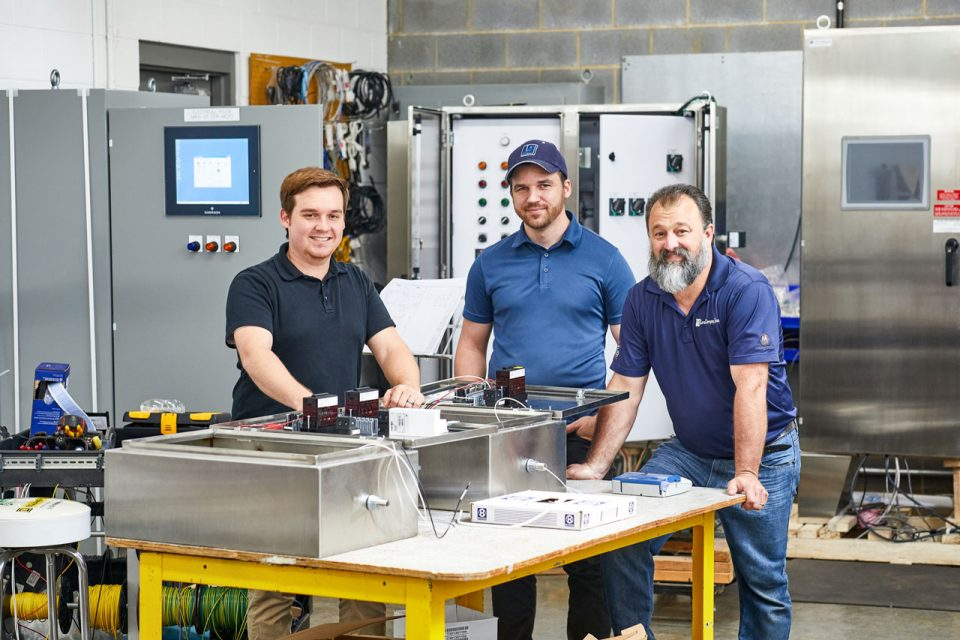 Three smiling male employees in the workshop at Lord & Company Industrial Automation