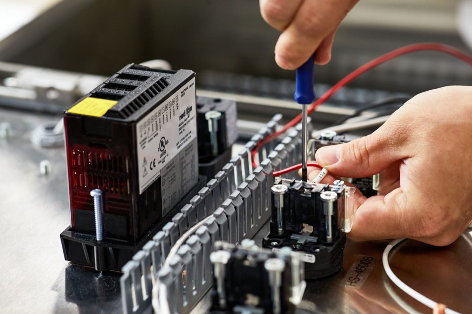 two male hands adjusting components of a mechanical control board with a screwdriver
