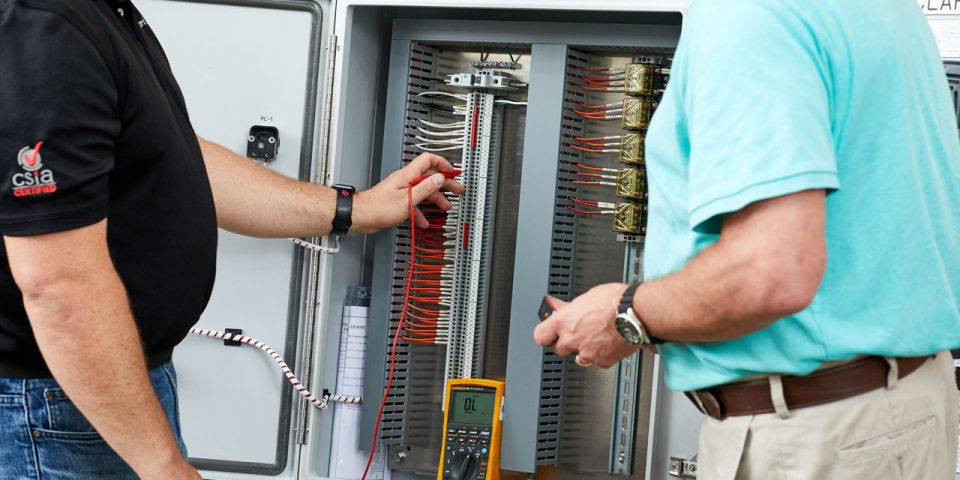Two men looking at the inside of a large mechanical control panel