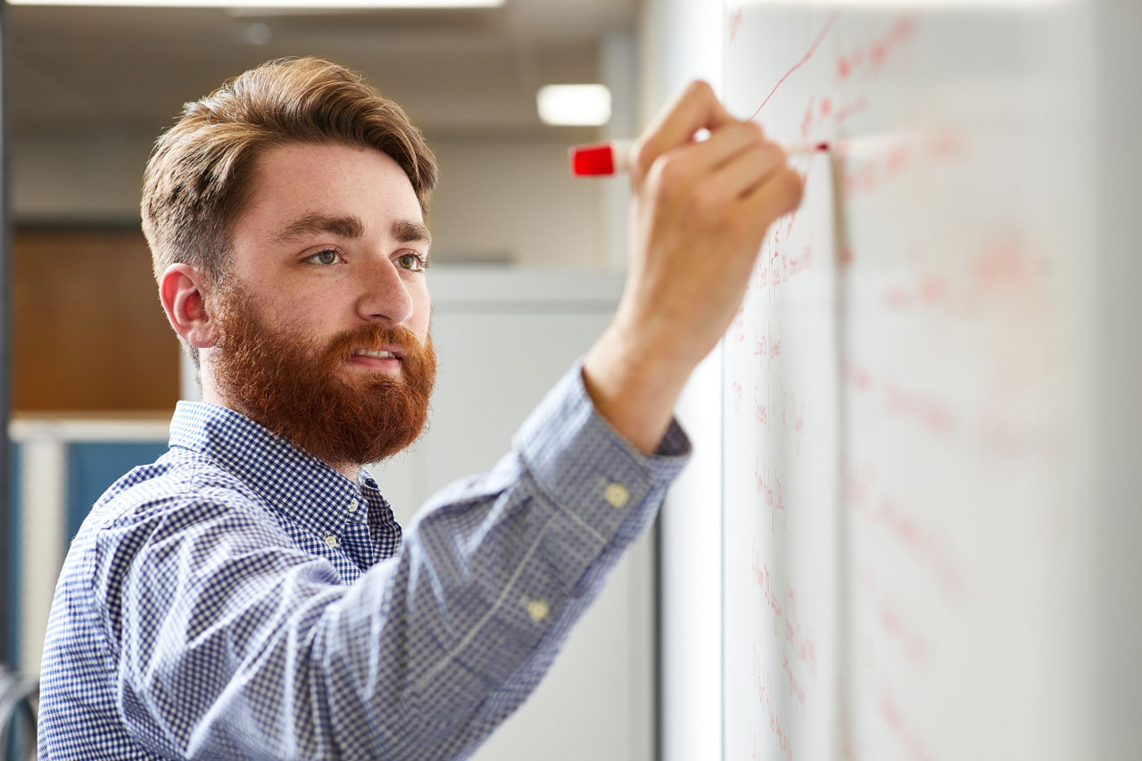 Young male professional with red hair and beard writing on a whiteboard