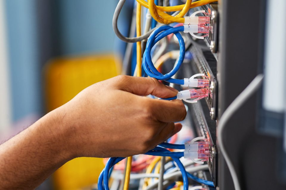A hand plugging a wire into a control panel with blue and yellow wires