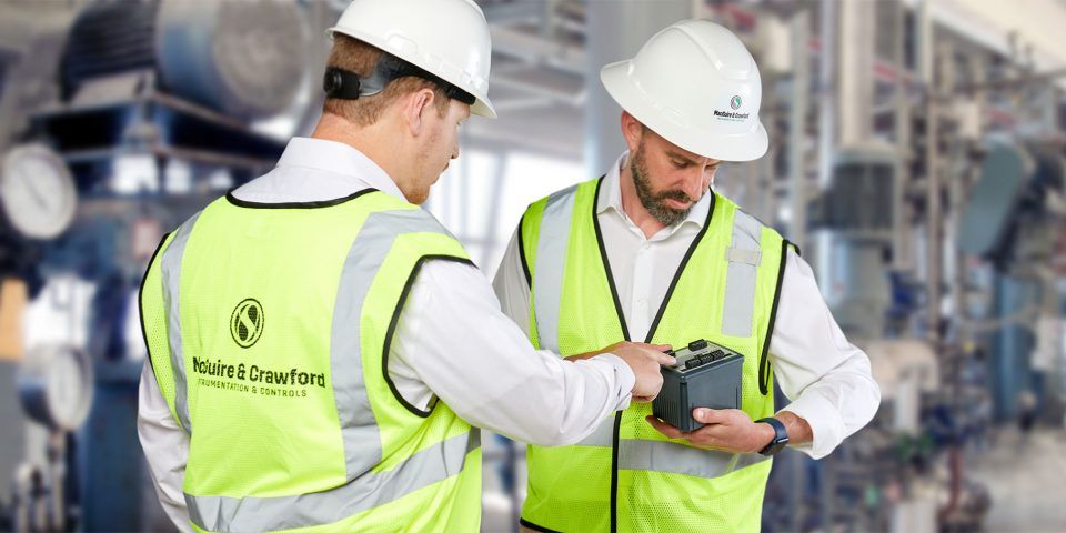 Two men wearing hard hats and yellow vests looking at a piece of instrumentation equipment