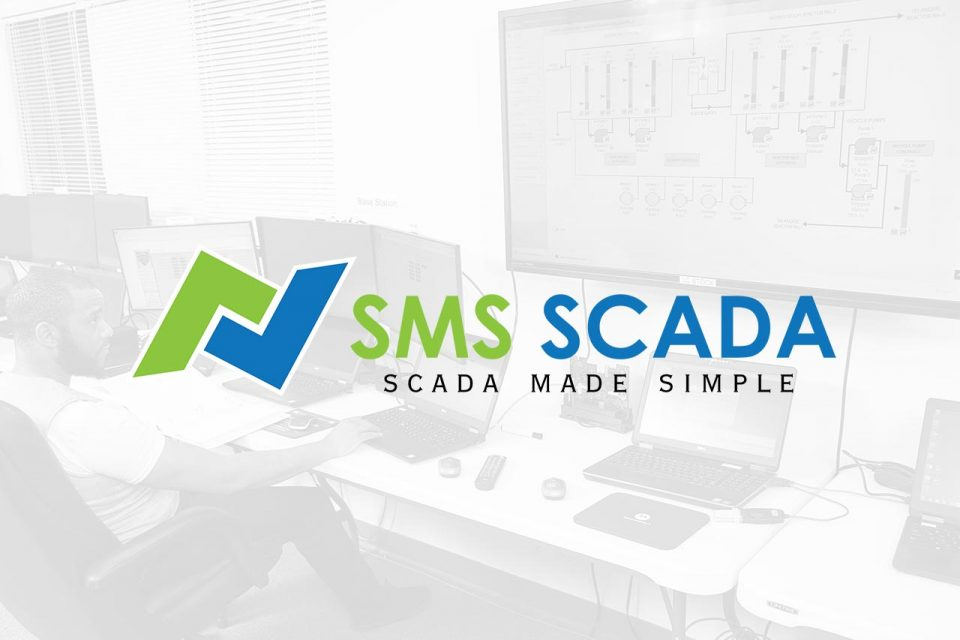 SMS SCADA logo imposed over a photo of a man working at a desk with multiple computer monitors