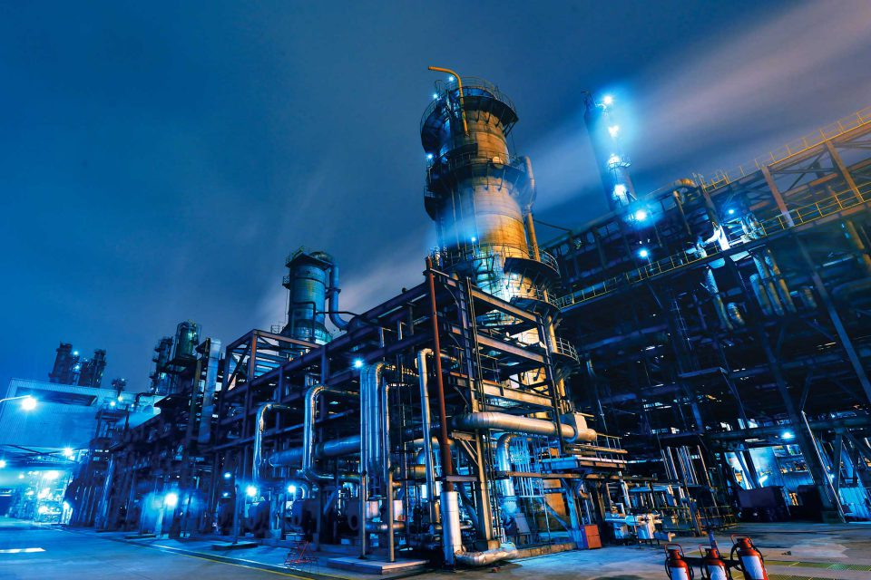 exterior of an industrial factory at dark with blue lights and fog
