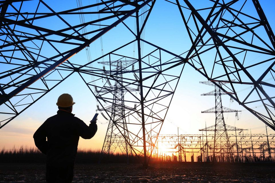 Male electricity worker standing in front of pylon silhouette