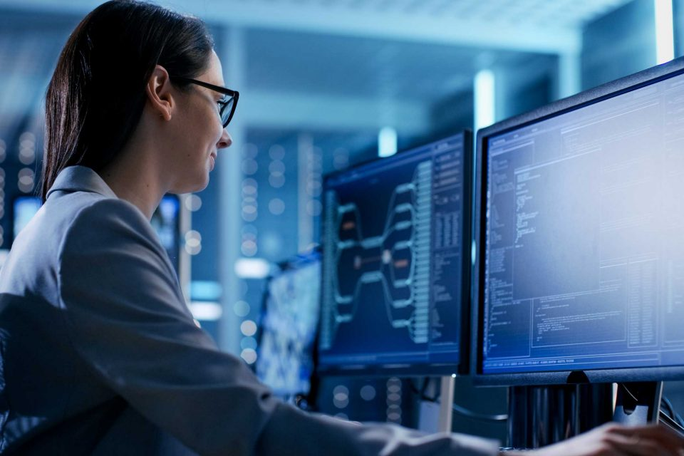 Close-up of Female IT Engineer Working in Monitoring Room with multiple displays