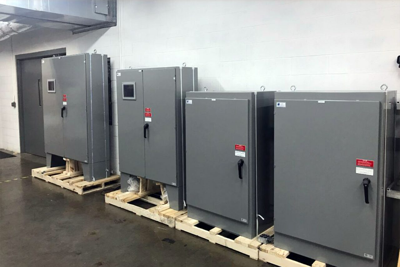 four large control panels with metal doors in a hallway